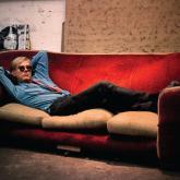 """Foto: Bob Adelman. Andy Warhol sentado en un sofá de terciopelo rojo en """"The Factory""""."""